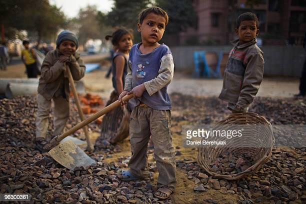 Indian children work nearby to their parents at a construction project in front of the Jawaharlal Nehru Stadium on January 30 2010 in New Delhi India...