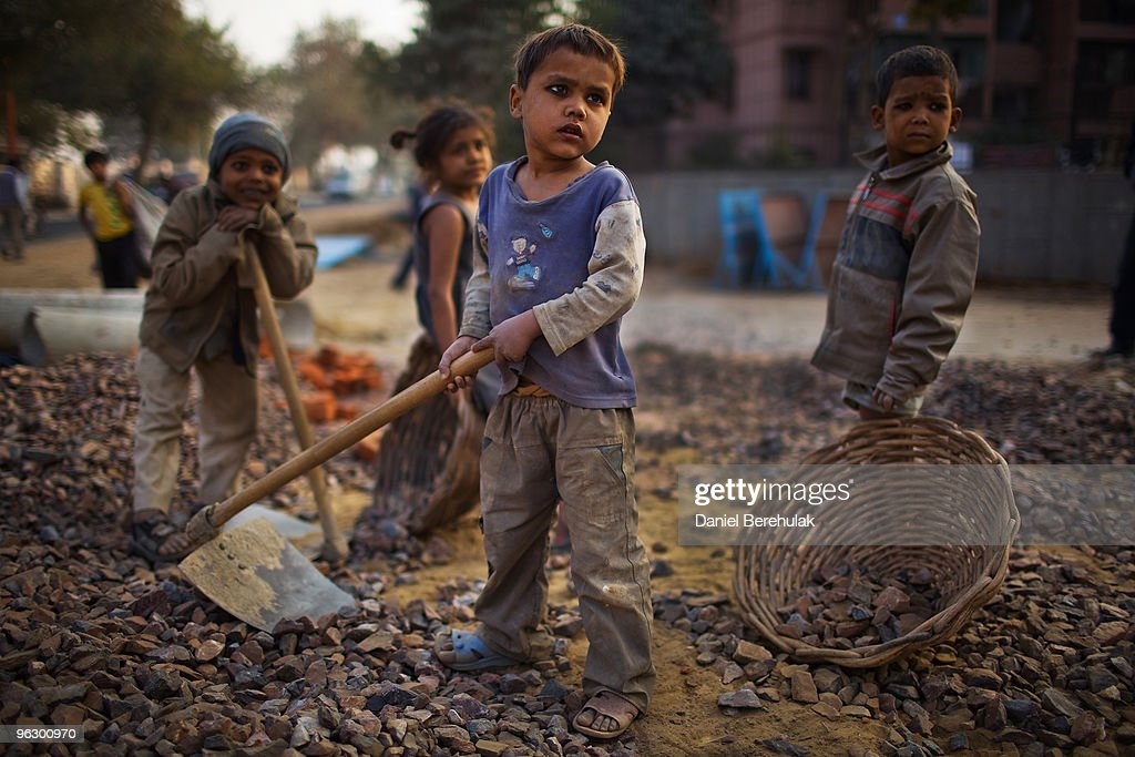 Indian children work nearby to their parents at a construction project in front of the Jawaharlal Nehru Stadium on January 30, 2010 in New Delhi, India. The children accompany their parents to the work site, where if they are prepared to work, they will receive money for bread an milk and be provided with dinner by the contractor. The Commonwealth Games are due to be held in the Indian capital from October 3-14, 2010, but concerns remain over construction of its sporting and transport infrastructure. The sheer scale of the project has drawn an enormous population of migrant workers from all over India. This week the High Court of Delhi has sought a response from the Government over the alleged failure to provide all the benefits of labour laws to workers involved in construction work for the coming Commonwealth Games. Workers are being paid below the minimum wage in order to complete these projects whilst also being forced to live and work under sub standard conditions.
