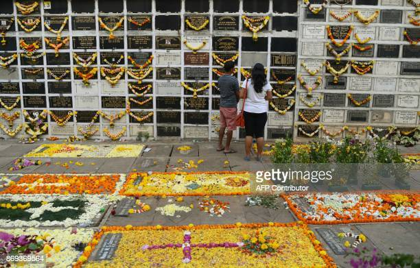 Indian Christian devotees pray near a plaque commemorating relatives on All Souls Day at the cemetery of a church in Mumbai on November 2 2017 All...