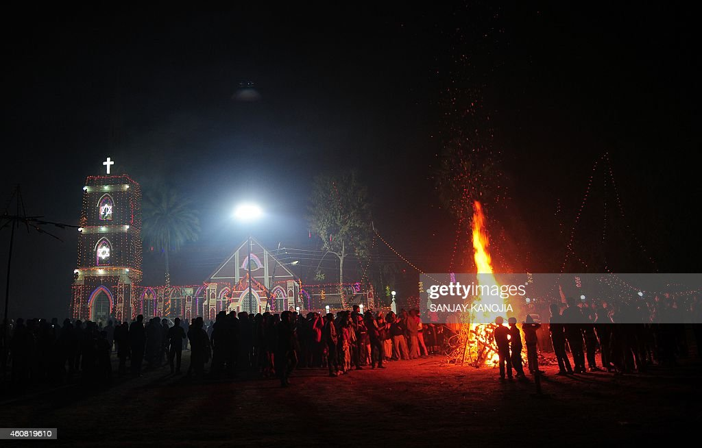 Indian Christian devotees stand beside a bonfire outside St Peter's Church in Allahabad on December 24 on Christmas Eve Despite Christians forming a...
