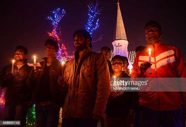 Indian Christian worshippers hold candles as they pose for a photograph while offering prayers at St Paul's church in Amritsar on December 222013...