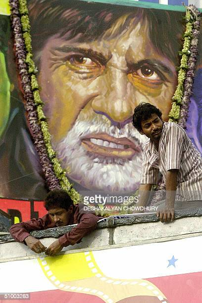 Indian cinema hall workers put the finishing touches to a hoarding promoting the film 'Deewaar' which stars screen legend Amitabh Bachchan in...