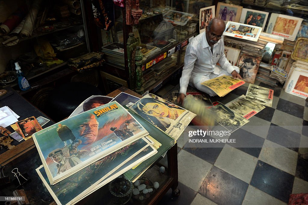 Indian cinema memorabilia dealer Shahid Mansoori sifts through posters for an order in his shop 'Mini Market' in Mumbai on April 30, 2013. One hundred years after the screening of a black-and-white silent film, India's brash, song-and-dance-laden Bollywood film industry celebrates its centenary later this week. The milestone will be marked with little fanfare, while India will be honoured as 'guest country' at next month's Cannes festival.