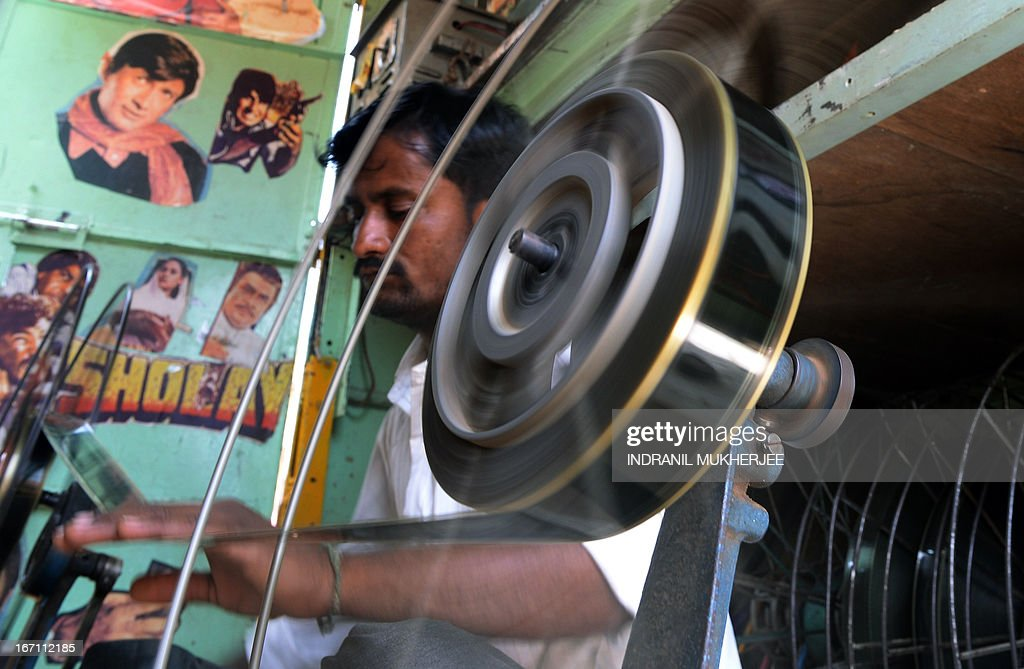Indian cinema projectionist Suhas, winds film roll onto spools inside his 'projection Truck' on the premises of the Anup Touring Talkies tent cinema at a ground in central Mumbai on April 20, 2013. To mark 100 years of Indian Cinema, a Marathi film 'Touring Talkies' is being screened in a makeshift tent theatre just like the days of yore, in its pre-multiplex and pre-single screen glory dating back 50 years. The tents, keeping in mind modern audiences, will have plush seating, air conditioning and popcorn and cola alongside fresh sugar-cane juice, roasted groundnuts and gram and pickle and other tit-bits. The cinema will screen four shows per day for a week. The idea of touring talkies was the brainchild of the doyne of Indian cinema, Dadasaheb Phalke, after he saw the British watching movies in tents. The touring cinema would travel through rural India and screen movies in makeshifts tents. At present, one can only find these talkies - whose sweltering tents and basic facilities contrast with the plush, air-conditioned multiplexes springing up in Indian cities, during Jatras (village fairs) in the interiors of the state. AFP PHOTO/ INDRANIL MUKHERJEE