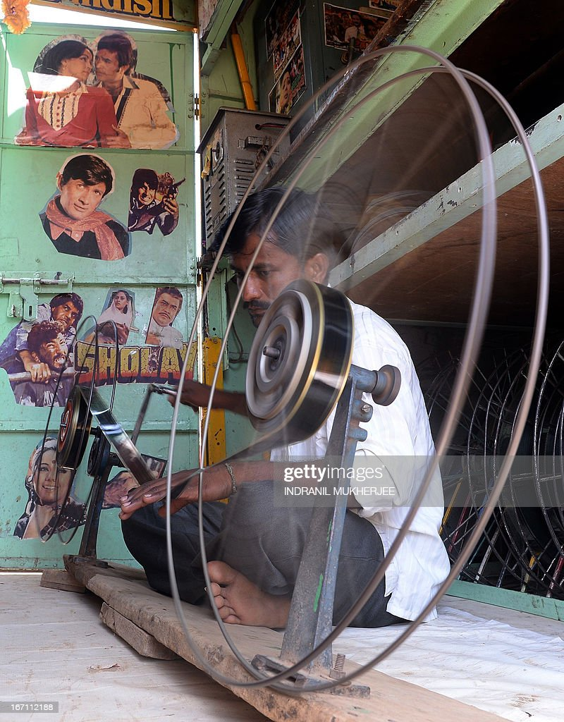 Indian cinema projectionist Suhas, winds film roll onto spools inside his 'projection Truck' on the premises of the Anup Touring Talkies tent cinema at a ground in central Mumbai on April 20, 2013. To mark 100 years of Indian Cinema, a Marathi film 'Touring Talkies' is being screened in a makeshift tent theatre just like the days of yore, in its pre-multiplex and pre-single screen glory dating back 50 years. The tents, keeping in mind modern audiences, will have plush seating, air conditioning and popcorn and cola alongside fresh sugar-cane juice, roasted groundnuts and gram and pickle and other tit-bits. The cinema will screen four shows per day for a week. The idea of touring talkies was the brainchild of the doyne of Indian cinema, Dadasaheb Phalke, after he saw the British watching movies in tents. The touring cinema would travel through rural India and screen movies in makeshifts tents. At present, one can only find these talkies - whose sweltering tents and basic facilities contrast with the plush, air-conditioned multiplexes springing up in Indian cities, during Jatras (village fairs) in the interiors of the state.