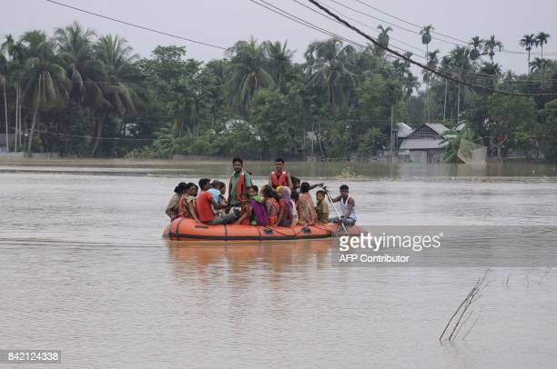 Indian civil defence personnel rescue villagers on a rubber boat at a flood affected village during heavy downpour at Baldakhal village in Agartala...