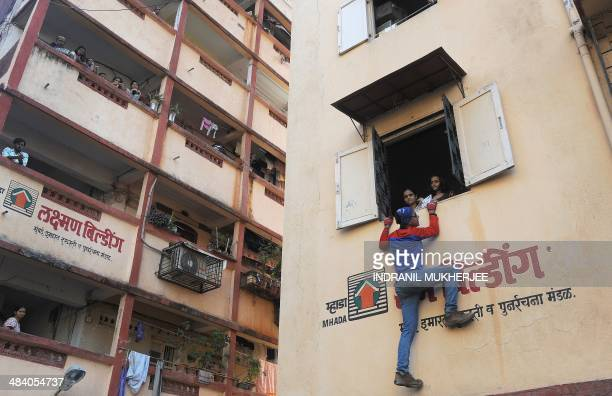 Indian climber and independent political candidate Gaurav Sharma wearing a 'spiderman' costume climbs to the window of a residential building and...