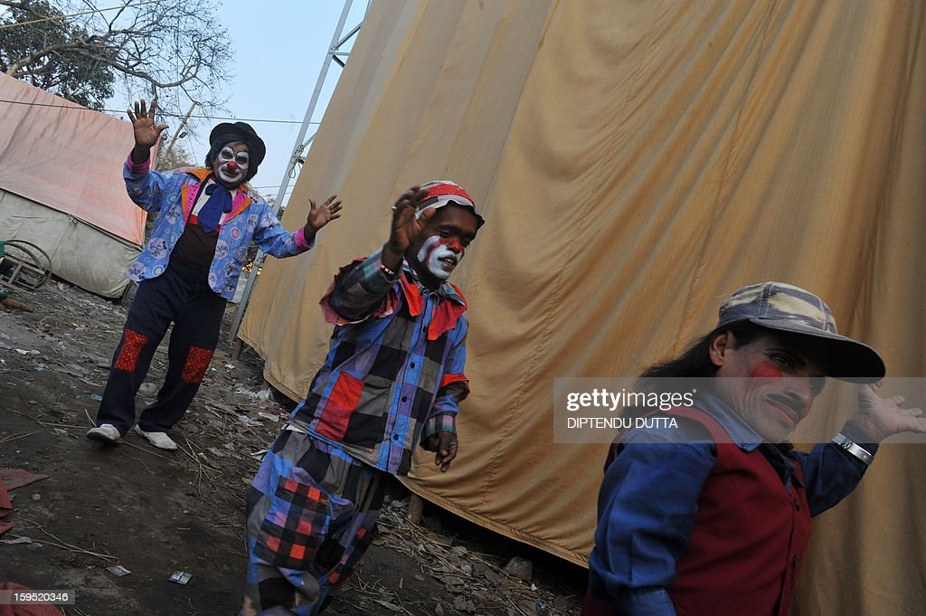 Indian clowns walk past a tent before preforming at the Kohinoor Circus in Siliguri on January 14, 2013. The Kohinoor Circus, inaugurated in 1988, is one of the most popular as it travels throughout India. At present, there are only ten circuses still active in India whereas in the first half of the 20th century, there were as many as 50 circuses touring the country. AFP PHOTO/ Diptendu DUTTA