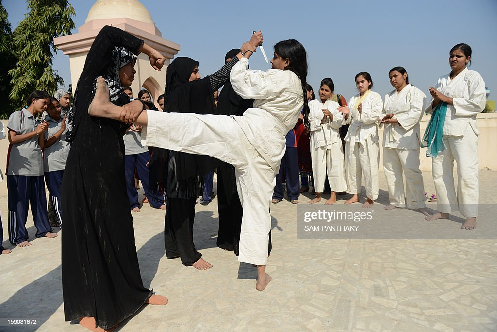 Indian college girls participate in a basic judo camp for self defense in Ahmedabad on January 5, 2013. Increasing crime against women and girls with the recent Delhi gang-rape and many similar crimes in Gujarat state are forcing women and girls to protect themselves with basic defence skills like judo and karate. AFP PHOTO / Sam PANTHAKY
