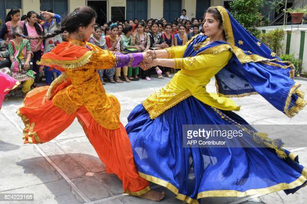 Indian college girls perform the Punjabi folk dance Giddha in traditional dresses during the Teej festival to mark the Sawan month at a women's...