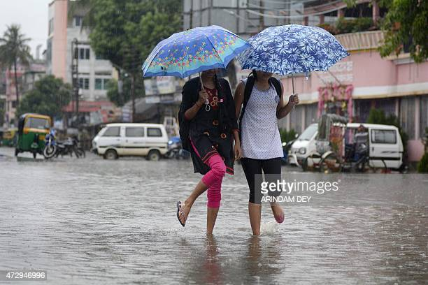 Indian college girls walks along a flooded street during a heavy downpour in Agartala the capital of northeastern state of Tripura on May 11 2015 AFP...
