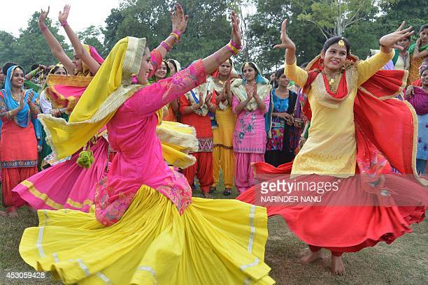 Indian college girls wear traditional Punjabi dress as they dance the 'giddha' during Teej festival celebrations on the occasion of Sawan Month at...