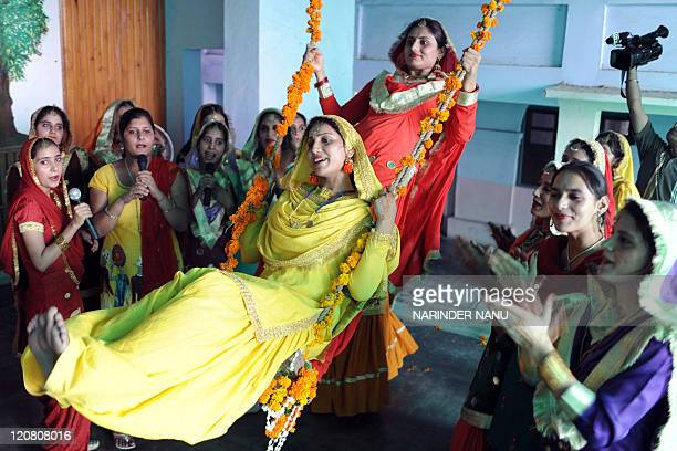 Indian college girls wearing traditional Punjabi swing as others swing during Teej festival celebrations at Khalsa college for women in Amritsar on...