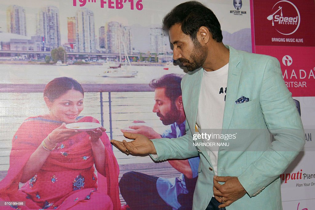 Indian comedian Binnu Dhillon poses next to an advertisement in Amritsar on February 14,2016, during promotional events for the forthcoming Punjabi film 'Channo Kamli Yaar Di'. / AFP / NARINDER NANU