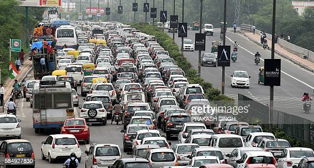 Indian commuters and their vehicles stand in a traffic jam in New Delhi on August 1 2016 / AFP / Prakash SINGH