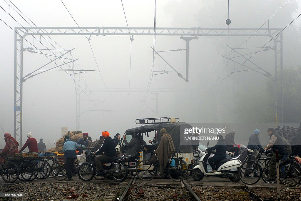 Indian commuters cross railway tracks through dense fog close to Amritsar Railway Station in Amritsar on December 29, 2012. Heavy fog has distrupted road, rail and air traffic across northern India.