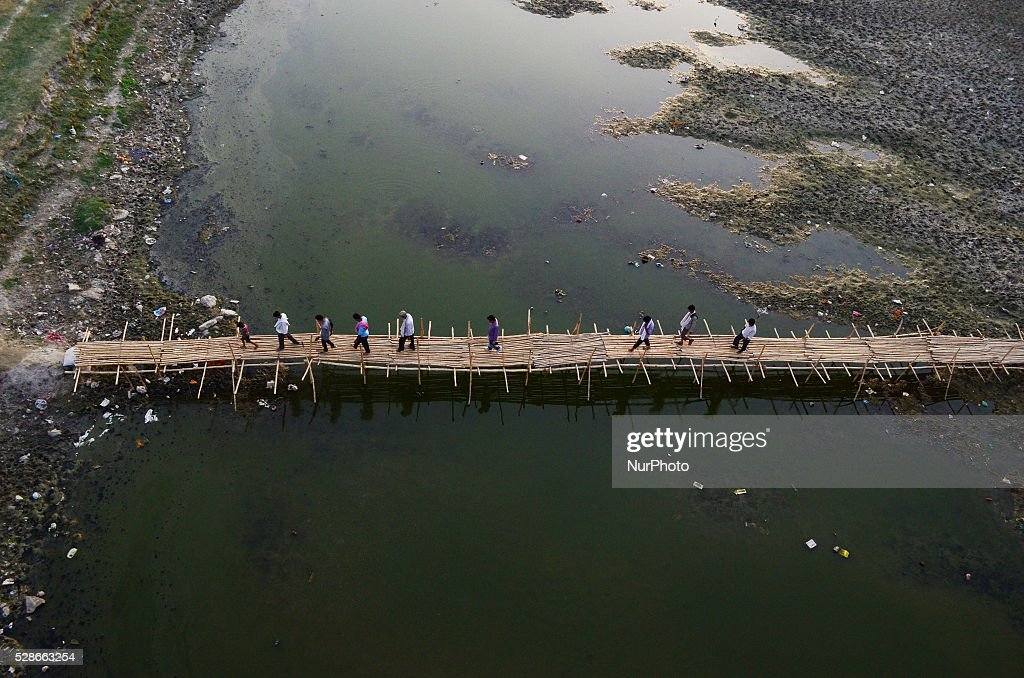 Indian commuters cross the partially dried Ganges River on a temporary bamboo bridge ,during a hot day in Allahabad on May 6,2016...Much of India is reeling under weekslong heat wave and severe conditions that have decimated crops, killed livestock and left atleast 330 millions indians without enough water for their daily needs.