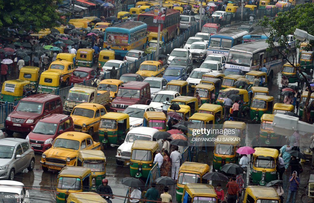 Indian commuters cross the road amid heavy rush hour traffic in Kolkata on July 31 2015 AFP PHOTO/ Dibyangshu Sarkar