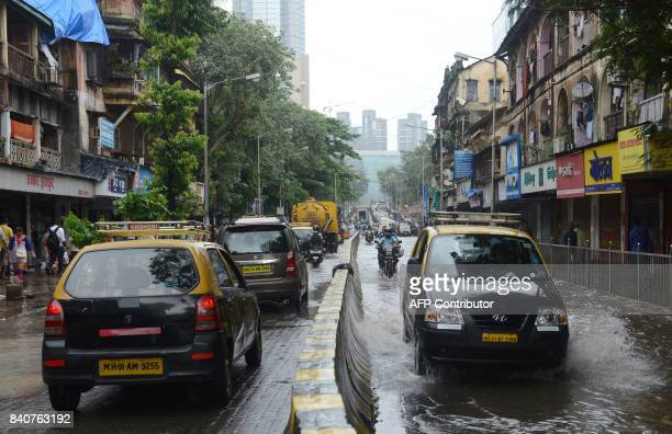 Indian commuters drive along a flooded road in Mumbai on August 30 after heavy rains brought major flooding to the coastal city At least five people...