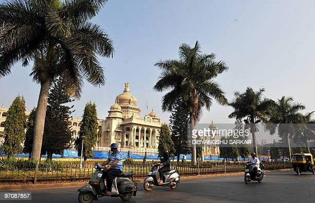Indian commuters drive their scooters past the Vidhana Soudha building in Bangalore on February 26 2010 Vidhana Soudha houses the Legislaive Chambers...