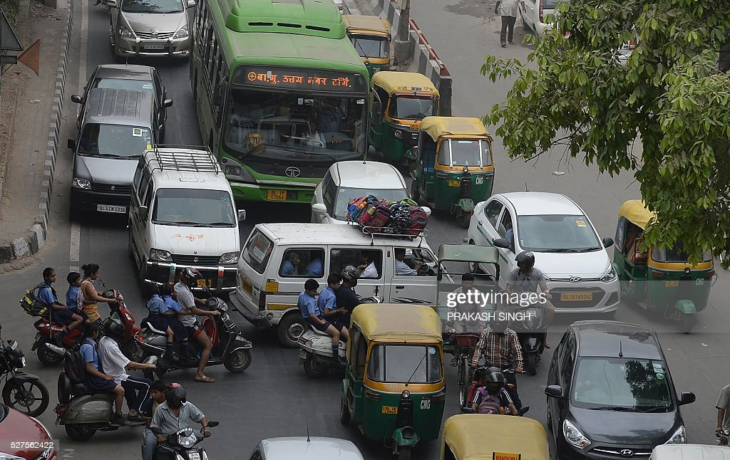 Indian commuters have their path crossed by a school van and parents on scooters as they drive the wrong way across a road to drop children at a nearby school creating a traffic jam in New Delhi on May 3, 2016. / AFP / PRAKASH