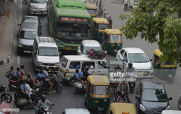 Indian commuters have their path crossed by a school van and parents on scooters as they drive the wrong way across a road to drop children at a...