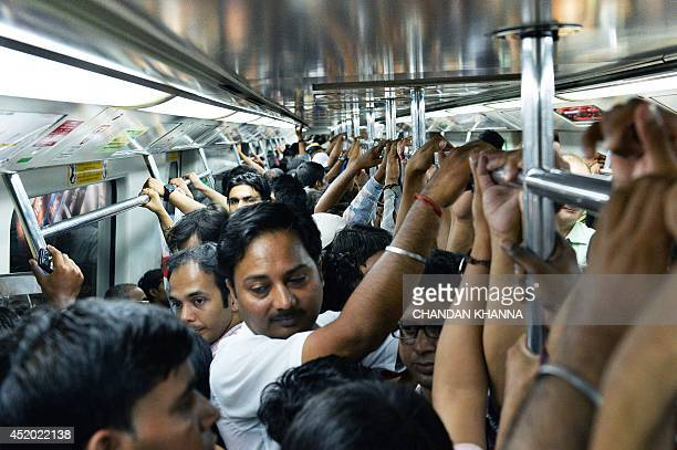 Indian commuters hold onto the rail inside a carriage of the metro train in New Delhi on July 11 on the occasion of World Population Day World...