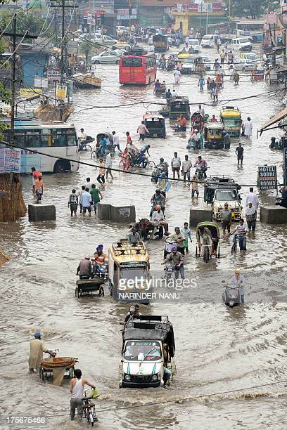 Indian commuters make their way along a flooded street after a heavy downpour in Amritsar on August 6 2013 The monsoon which covers the subcontinent...