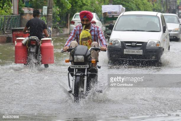 Indian commuters make their way along a flooded street after heavy rain in Amritsar on June 29 2017 / AFP PHOTO / NARINDER NANU