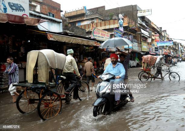 Indian commuters make their way along a flooded street in Amritsar on September 5 after heavy monsoon rainfall struck the northern Indian city Heavy...