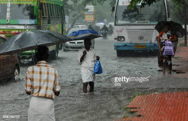 Indian commuters make their way along a waterlogged road during heavy monsoon rains in Kochi on June 08 2016 Annual monsoon rains arrived in southern...