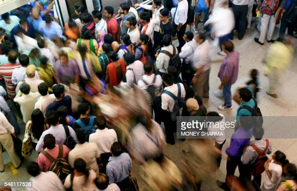 Indian commuters make their way through a metro station at rush hour in New Delhi on July 11 on World Population Day Indias population of 13 billion...