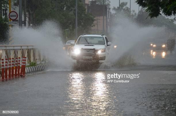 Indian commuters make their way through heavy monsoon rain in Amritsar on June 28 2017 / AFP PHOTO / NARINDER NANU