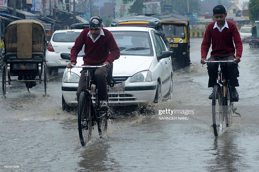 Indian commuters make their way through heavy rain in Amritsar on February 23, 2013. Temperatures in the city reached about 12 degrees celsius. AFP PHOTO/NARINDER NANU