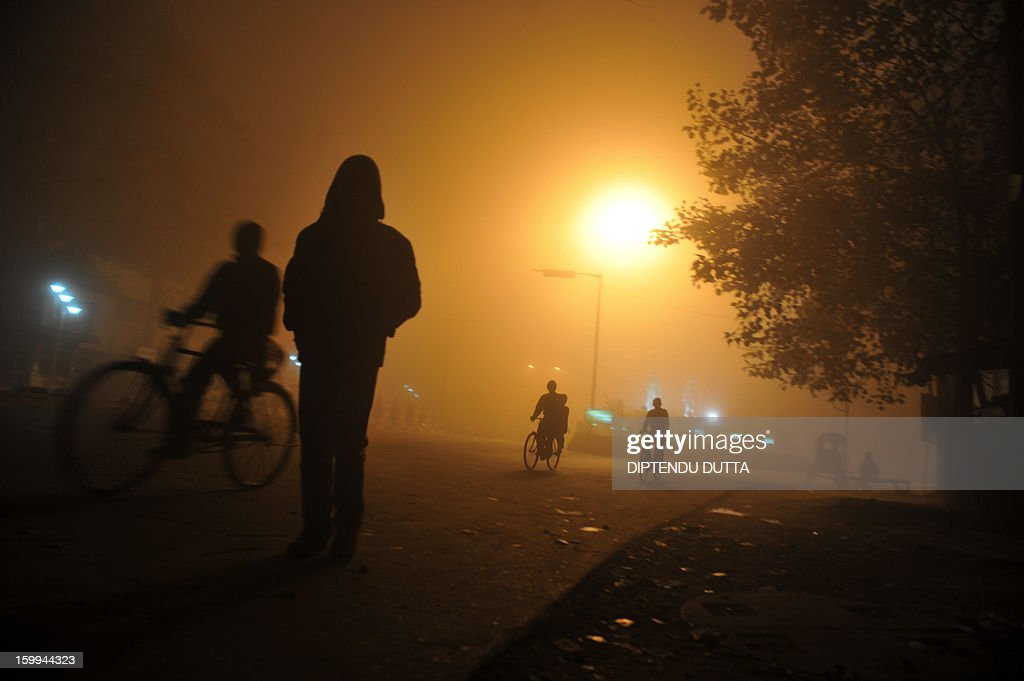 Indian commuters make their way through thick fog along a road during a foggy night in Siliguri on January 24, 2013. As thousands of homeless people sought places in temporary shelters, the unusual cold throughout India has been attributed to dense fog which has obscured the sun and disrupted airports and trains, as well as icy winds from the snowy Himalayas to the north.AFP PHOTO/Diptendu DUTTA