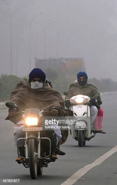 Indian commuters make their way through thick fog on the outskirts of Amritsar on December 19 2013 Winter fog in parts of northern India has...