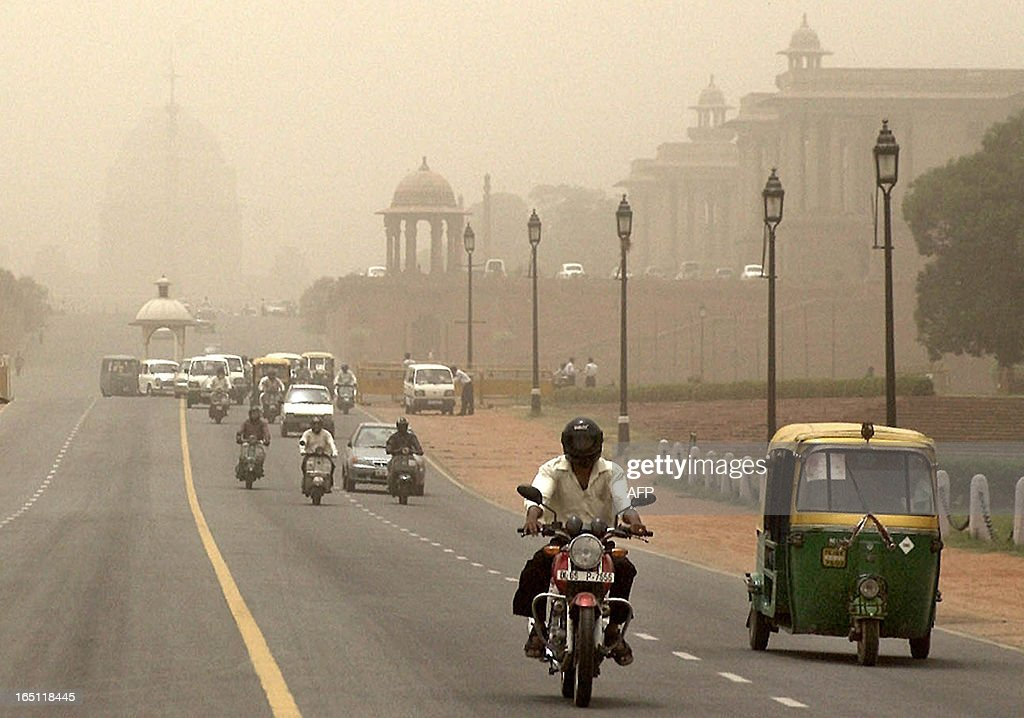Indian commuters pass government buildings engulfed by a dust storm in New Delhi 06 June 2003 preceeded by rains which brought down temperatures by...
