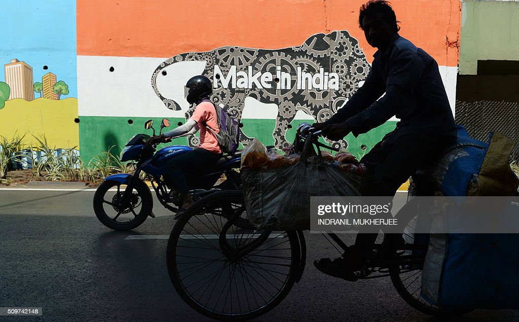 Indian commuters ride past a wall bearing the image of the mascot for 'Make in India Week' in Mumbai on February 12, 2016. Over 190 companies, and 5,000 delegates from 60 countries, are due to take part in the first 'Make in India' week to be held in Mumbai from February 13-18. AFP PHOTO / INDRANIL MUKHERJEE / AFP / INDRANIL MUKHERJEE