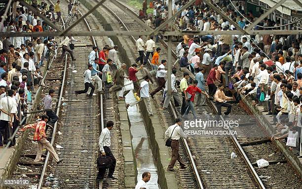 Indian commuters run across railway tracks to catch a local train after a announcement was made that the train was to arrive on the platform opposite...