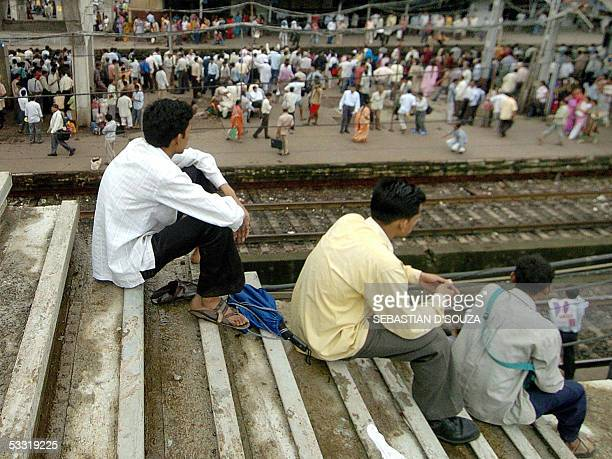 Indian commuters sit on a under construction footbridge as they wait the arrival of a local train at Ghatkopar Station in Central Mumbai 03 August...