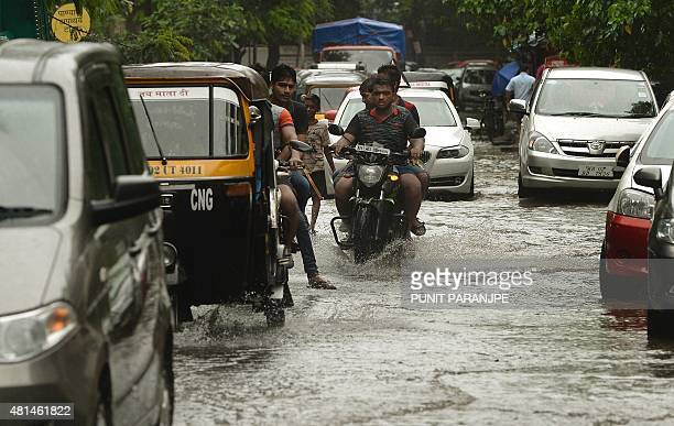 Indian commuters travel along a flooded street following rain showers in Mumbai on July 21 2015 AFP PHOTO/ PUNIT PARANJPE