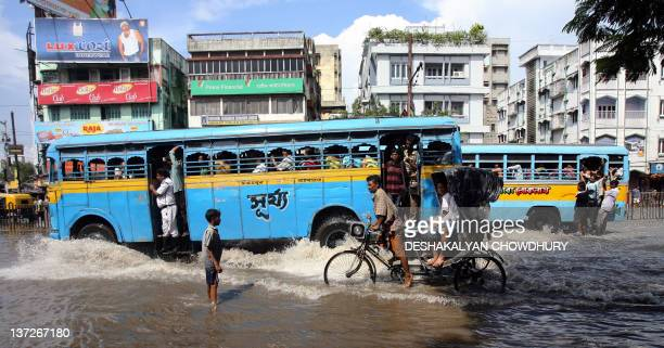 Indian commuters travel along a flooded street in Kolkata 26 September 2007 Following 36 hours of a heavy monsoon downpours many streets of the...
