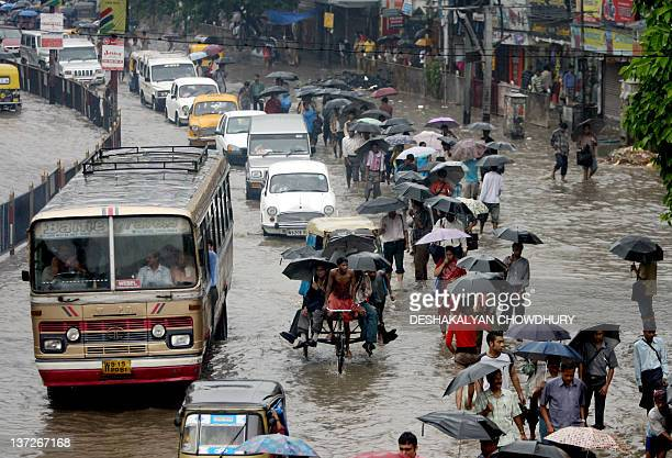 Indian commuters travel along a flooded street of Kolkata 13 June 2007 Heavy monsoon downpours have seriously affected daily life in the eastern...
