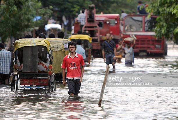 Indian commuters travel along a waterlogged stretch of road at Bangur in Kolkata 28 September 2007 Twenty eight people died in the recent rains and...