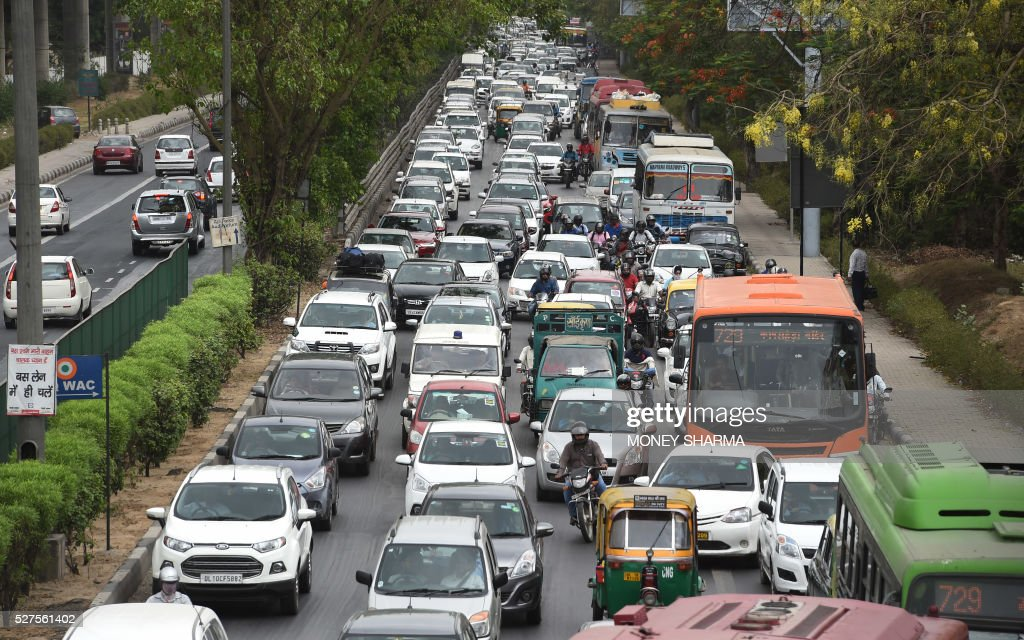 Indian commuters travel in a traffic jam on their way to Gurgaon from New Delhi on May 3, 2016. The Indian capital is witnessing massive jams for a second day as taxi drivers protest the ban on diesel cab after India's Supreme court order banning diesel cabs from plying the roads of the world's most polluted capital. The ban impacted some 27,000 diesel taxis registered in Delhi, including app-based cab operators Ola and Uber. / AFP / MONEY