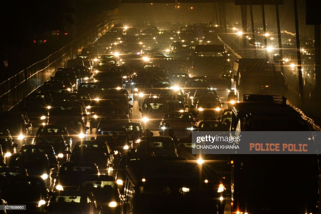 Indian commuters travel through a traffic jam on their way to New Delhi from Gurgaon on May 3, 2016. Hundreds of taxi drivers protested in New Delhi on May 2 against a ban on diesel cabs, the latest initiative aimed at improving air quality in the world's most polluted capital. India's top court on April 30 ordered taxis run on the dirty fuel off the city's roads, refusing industry requests for more time to switch to greener compressed natural gas (CNG). Many of Delhi's taxis already run on CNG, but the ban will impact about 30,000 traditional cabs and some working for app-based Uber and Ola services, according to taxi operators. / AFP / CHANDAN