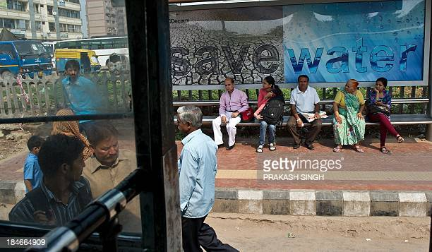 Indian commuters wait at a bus stop with a billboard advocating water conservation in New Delhi on October 15 2013 India plans to spend 110 billion...