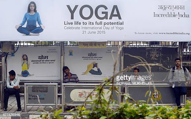 Indian commuters wait at a bus stop with an advertisement for the upcoming International Day of Yoga in Mumbai on June 17 2015 Events will be held...