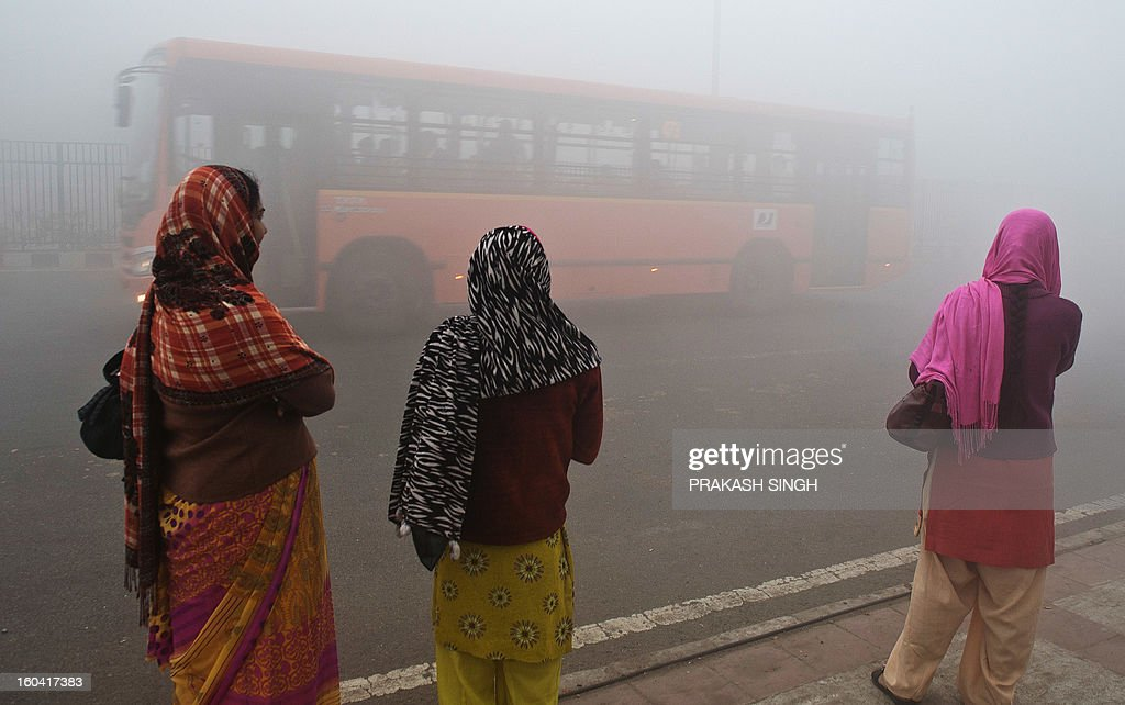 Indian commuters wait for a bus early on a polluted morning in New Delhi on January 31, 2013. Air Quality Index (AQI) pollution markers were at hazardous levels around the city. AFP PHOTO/ Prakash SINGH