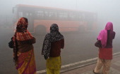 Indian commuters wait for a bus early on a polluted morning in New Delhi on January 31 2013 Air Quality Index pollution markers were at hazardous...